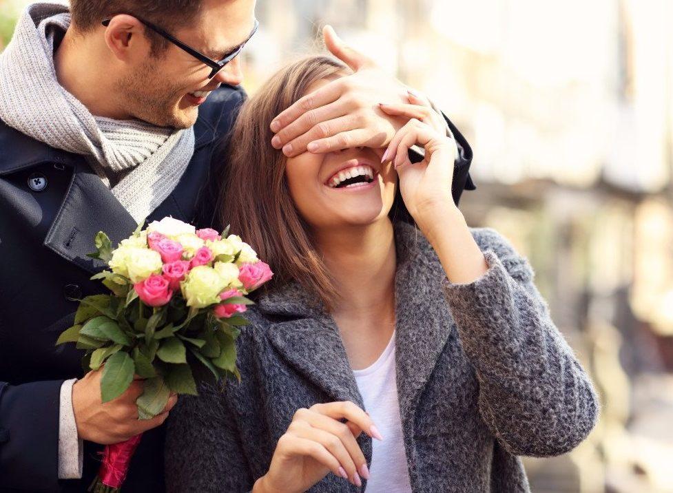 Homme avec un bouquet cachant les yeux d'une femme